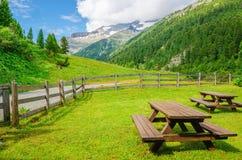 Träbänkar som har picknick i den alpina dalen, Österrike Arkivbild