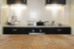 Träbästa tabell med suddig kökinrebakgrund Arkivfoton