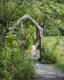 Träbåge på en trädgårds- bana arkivfoton