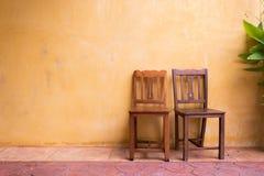 Träbakgrund för stol- och cementmortelvägg arkivfoton