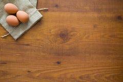 Träbakgrund med ägg Fotografering för Bildbyråer