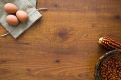 Träbakgrund med ägg, havremajskolvar och korn Royaltyfri Fotografi