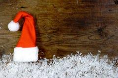 Träbakgrund med det santa locket, snö på gränsen och copyspa Fotografering för Bildbyråer