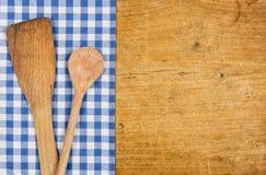 Träbakgrund med en blå rutig bordduk och träsked Arkivbild