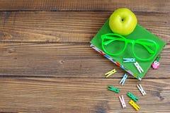 Träbakgrund med en bok och exponeringsglas äpple - green Top beskådar Royaltyfri Fotografi