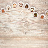 Träbakgrund med en rad av choklader, utrymme Arkivbild