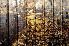 Träbakgrund med guld- vatten och bubblor Royaltyfri Bild