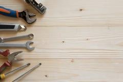 Träbakgrund med hjälpmedel Baner för ett maskinvarulager och en byggfirma Skruvmejslar plattång, elektriskt band royaltyfria bilder