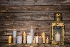 Träbakgrund in med många brännande stearinljus och ett gammalt lantligt Arkivfoto