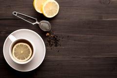 Träbakgrund med svart te, citronen och honung arkivfoton