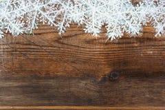Träbakgrund med vintersnö på gränsen och copyspacen Royaltyfria Bilder