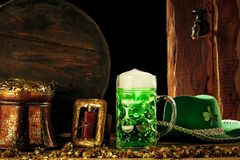 Träbakgrunden med massor av guld- mynt och ett stort rånar av öl med en grön pilbåge arkivfoto