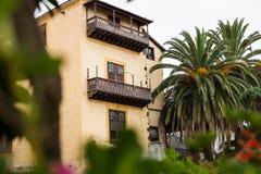 Träbalkonger på hus mellan palmträd i La Orotava, Tenerife, Spanien Arkivbilder
