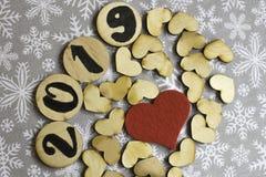 Träbeståndsdelar med numret 2019, trähjärtor och en klädde med filt röd hjärta på begrepp för nytt år för snöflingabakgrund royaltyfria bilder