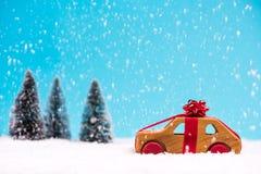 Träbil i rött band, jul gåva eller försäljning arkivfoton