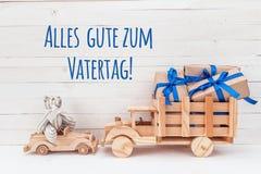 Träbil med nallebjörnen och trälastbilen med gåvor TyskG Royaltyfria Bilder