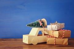 Träbil som bär ett julträd och gåvor Royaltyfri Foto