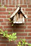 träbirdhousetegelstenvägg Arkivfoto