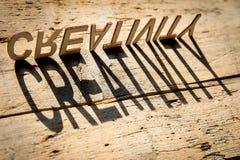 Träbokstäver bygger ordkreativiteten Arkivfoto