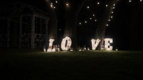 Träbokstäver med kulaljus Ord - förälskelse Upplyst ord FÖRÄLSKELSE på etappen Ordet älskar att bestå av ljus på lager videofilmer