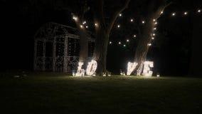 Träbokstäver med kulaljus Ord - förälskelse Upplyst ord FÖRÄLSKELSE på etappen Ordet älskar att bestå av ljus på arkivfilmer