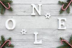 Träbokstäver Noel på julbakgrund Arkivfoto