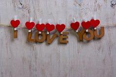 Träbokstäver och hjärta som bildar uttryck ÄLSKAR JAG, DIG Royaltyfria Foton