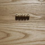 Träbokstäver som stavar mars på en träbakgrund arkivbilder
