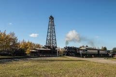 Träborra rigg med en övergående steamtrain arkivbild