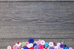 Träbräde för kulöra knappar, färgrika knappar, på gammalt trä Royaltyfria Bilder