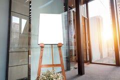 Träbräde med den tomma affischen, skärmgolvställning i banret som annonserar begrepp i ingång av hotellet Åtlöje upp tolkning 3D  royaltyfri bild