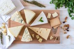 Träbräde med olika sorter av läcker ost med muttrar arkivfoto