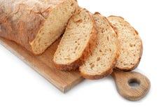 Träbräde med skivat nytt smakligt bröd på vit bakgrund arkivbild