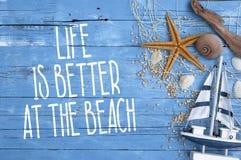 Träbrädet med maritim garnering och liv är bättre på stranden royaltyfri bild