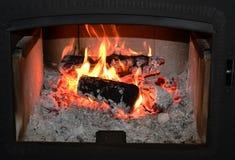 Träbränning i en hemtrevlig spis hemma i inre Spis som ett stycke av möblemang Jul royaltyfri fotografi