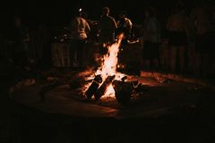 Träbränning i ett sent - nattlägereldfolk i bakgrunden royaltyfri foto