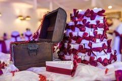 Träbröstkorg på tabellen med en violett bordduk och små gåvor för gäster från nygifta personerna arkivbild