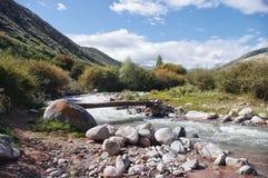 Träbro över en bergflod i Kirgizistan Royaltyfri Bild