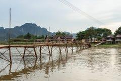 Träbro över flodsång till flodstrandgästhemmet Arkivbild