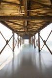 Träbro över havet på Kassandra Beach, låg siktspunkt med suddiga vågor eller vatten Alanya Turkiet dng arkivfoto