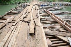 Träbro över kanalen för trafik mellan byar i grannländer av Thailand royaltyfri foto