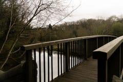 Träbro över vatten av dekanen arkivfoto