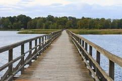 Träbro för gångare på Sirvenos sjön royaltyfri foto