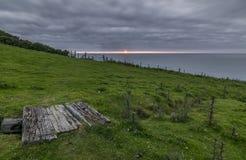 Träbro för kust- bana, med en molnig himmel och en ljus solnedgång Arkivfoto