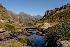 Träbro i den fotvandra slingan Estanys de Tristaina, Pyrenees, Andorra royaltyfria foton