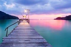 Träbro i porten över havet mellan solnedgången Arkivbild