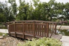 Träbro nära sjön i parkera Arkivfoto