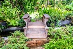 Träbro och ström i trädgård Royaltyfria Foton