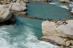 Träbro ovanför spring för ström för flodvatten mellan stenar Royaltyfri Fotografi