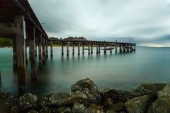 Träbro på det silkeslena havet med silkeslena regnmoln Royaltyfri Fotografi